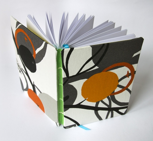 Handmade book with exposed spine and green accordion spacing